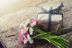 Photo illustration: flowers and a gift pack. This is not a sample of Massage Gift Card by Massaaži Ekspress.